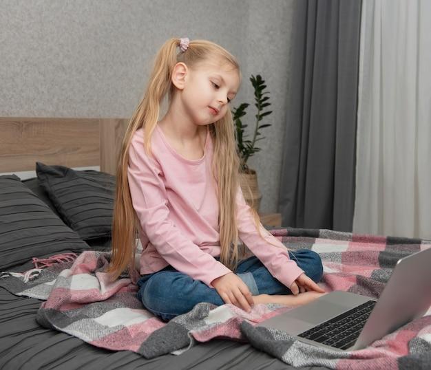 ブロンドの女の子はベッドの上のラップトップでオンラインで自宅で勉強