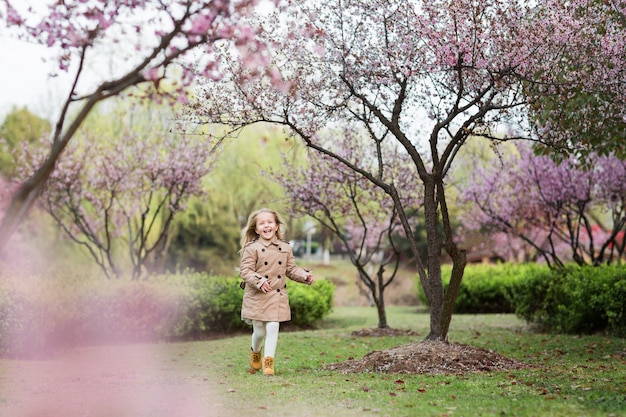 Blonde girl in stylish clothes playing and running in the cherry blossom garden.