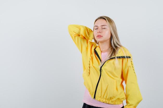 Ragazza bionda che soffre di dolore al collo in giacca gialla e sembra stanca