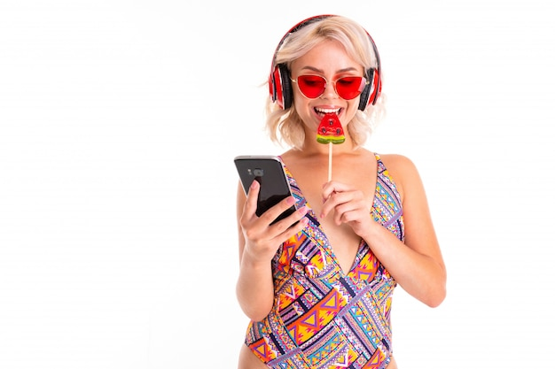Blonde girl in a swimsuit and sunglasses with a lollipop and a phone in her hands on of a swimming mattress