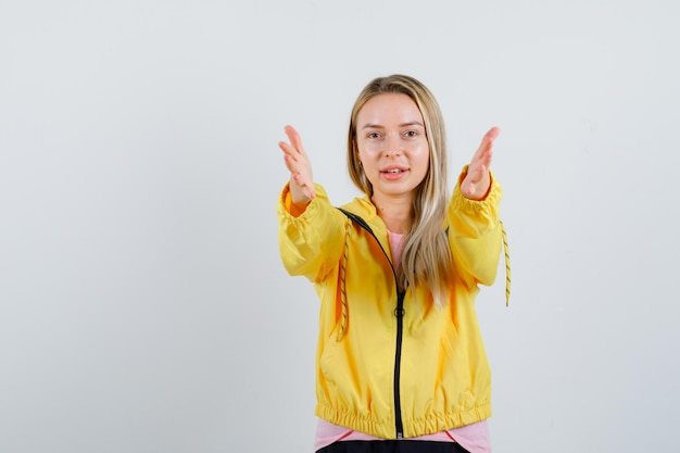 Blonde girl in t-shirt, jacket keeping hands outstretched and looking confident
