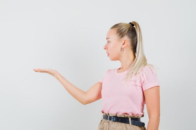 Ragazza bionda in t-shirt, pantaloni che guardano il suo palmo aperto da parte e che sembra concentrata, vista frontale.