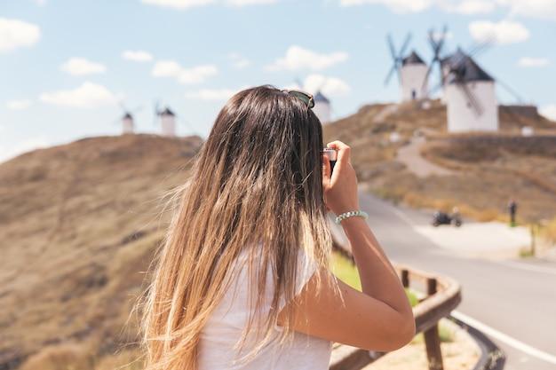 La mancha의 풍차에서 사진을 찍는 금발 소녀. 백그라운드에서 전통적인 풍차입니다.