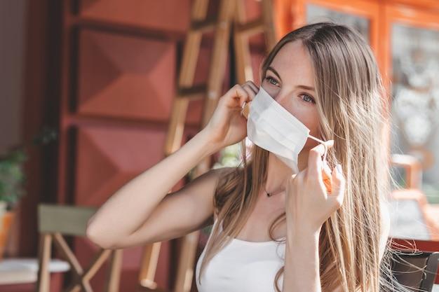 ブロンドの女の子が医療用マスクを脱いで、路上の都市のカフェに座っています。