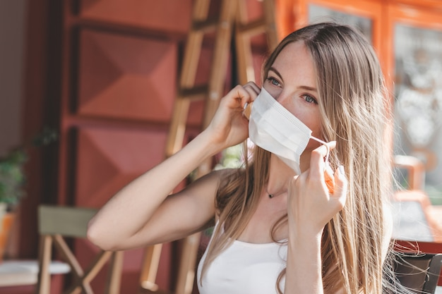 Blonde girl taking off a medical mask and sitting in a city cafe on the street