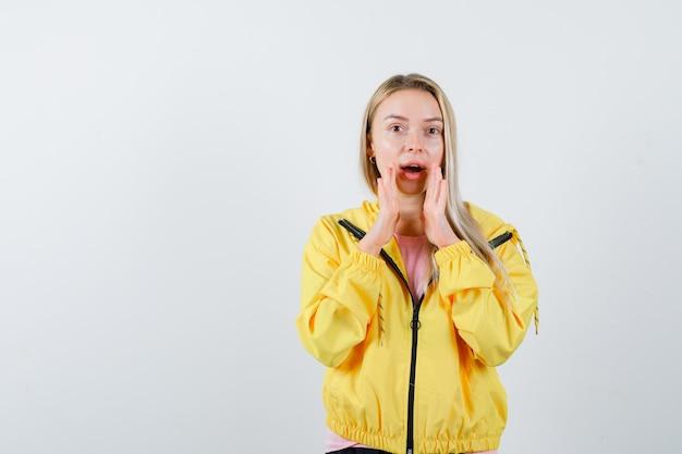 노란색 재킷에 입을 열고 가까이 손으로 비밀을 말하고 놀란 금발 소녀.