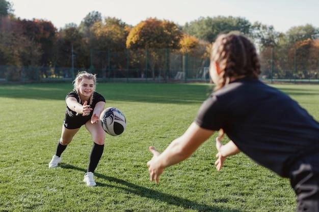팀 동료에게 공을 던지는 금발 소녀