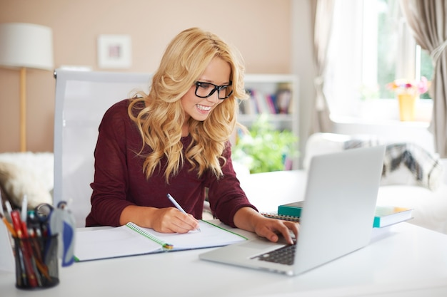 Blonde girl using laptop during studying at home