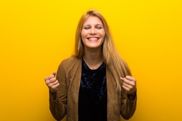 Blonde girl on vibrant yellow background celebrating a victory in winner position