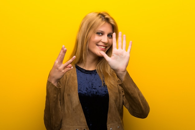 Blonde girl on vibrant yellow background counting eight with fingers