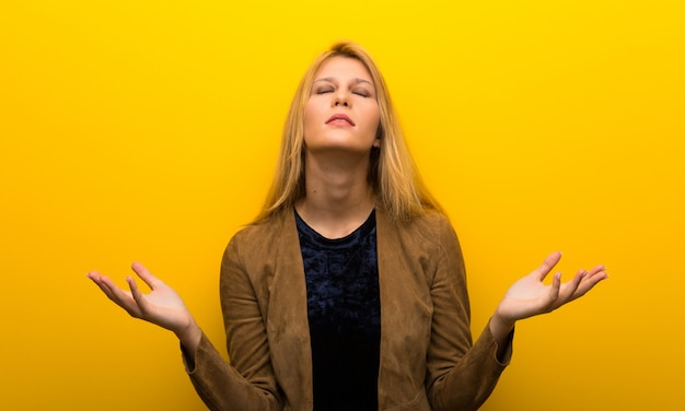 Blonde girl on vibrant yellow background frustrated by a bad situation