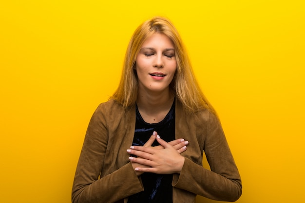 Blonde girl on vibrant yellow background having a pain in the heart