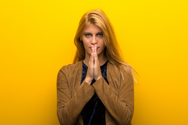 Blonde girl on vibrant yellow background keeps palm together.
