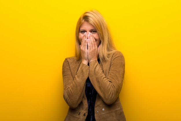 Blonde girl on vibrant yellow background smiling a lot while covering mouth