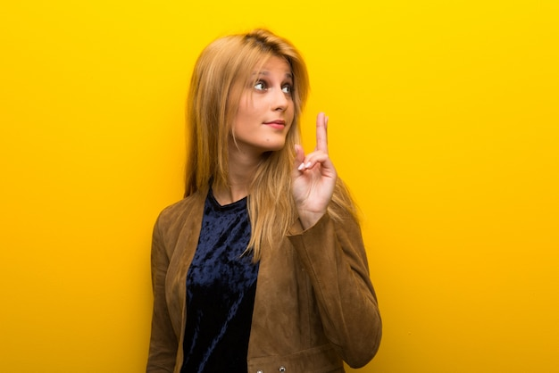Blonde girl on vibrant yellow background with fingers crossing and wishing the best
