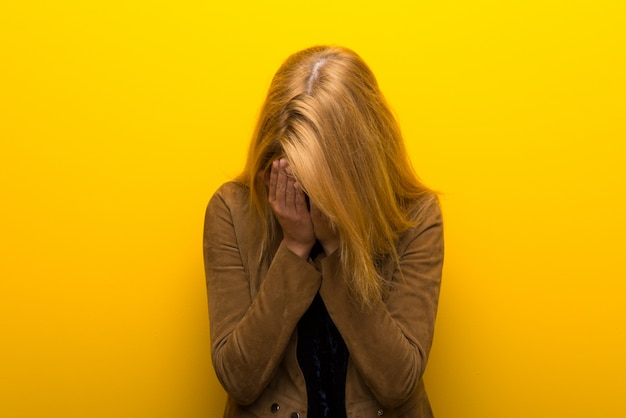 Blonde girl on vibrant yellow background with tired and sick expression