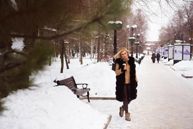 冬の通りを歩いてブロンドの女の子