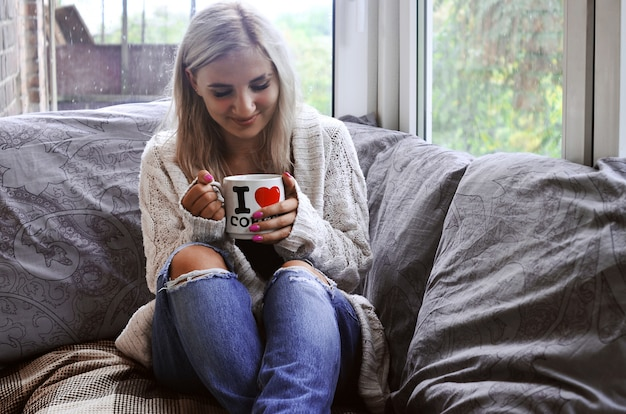 Blonde girl in a warm sweater with a cup of coffee