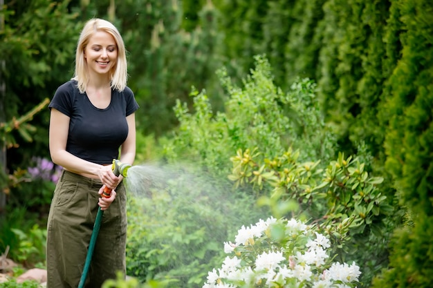 夏に彼女の庭に水をまくブロンドの女の子