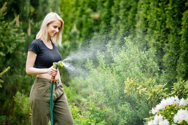 Blonde girl watering her garden in summer