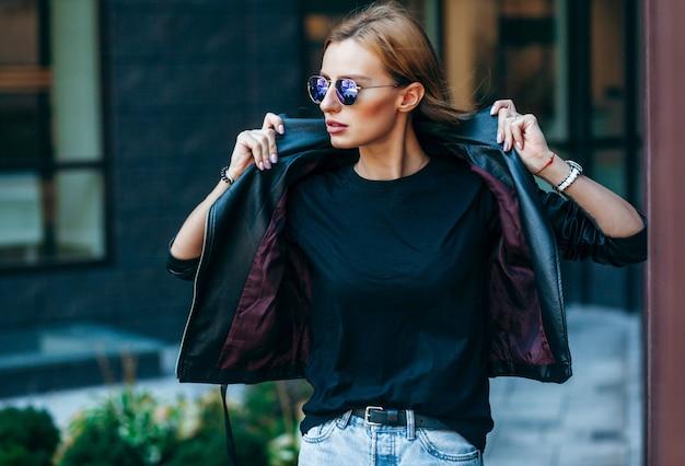 Блондинка в черной футболке, очках и кожаной куртке позирует на улице