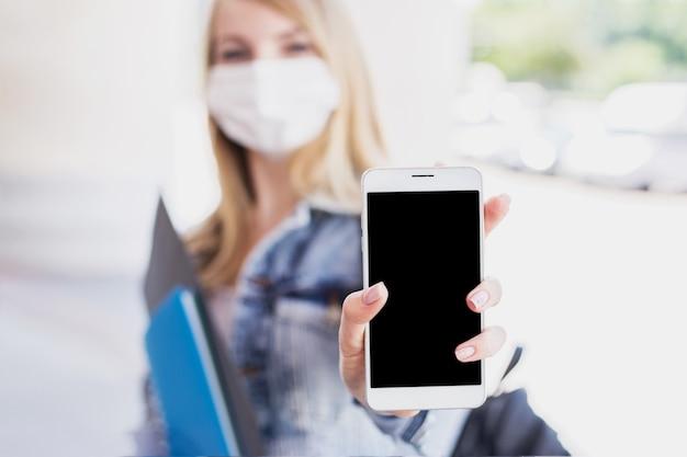 医療マスクを身に着けているブロンドの女の子は携帯電話の空白の画面を示しています