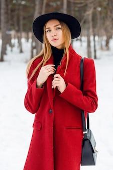 Блондинка в красном пальто на снежном поле