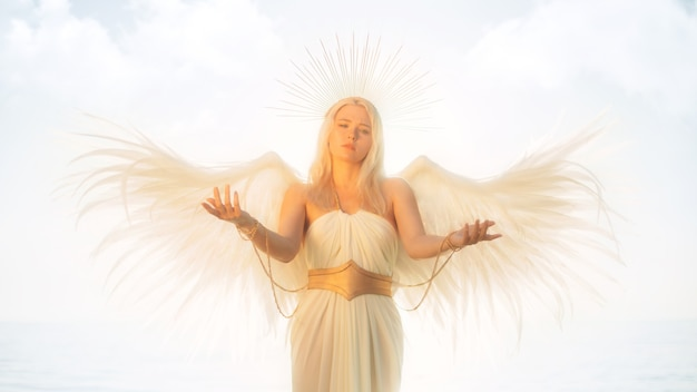 Blonde girl in a white angel costume against the background of the sky