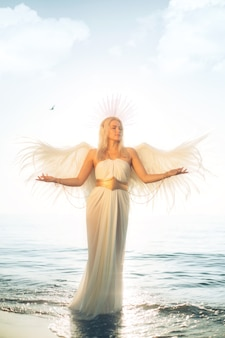Blonde girl in a white angel costume near the sea against the background of the sky