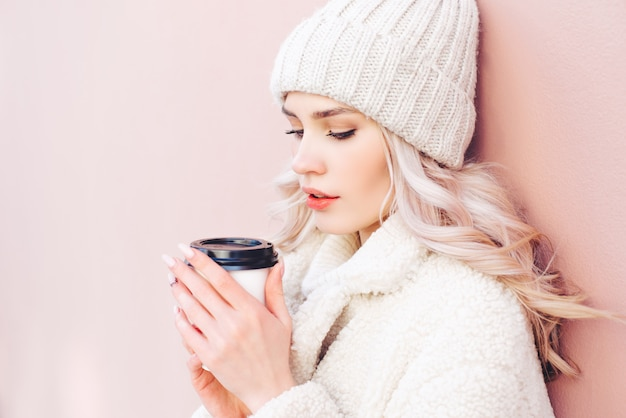 The blonde girl in winter clothes is holding a coffee in a paper cup on a pink background.