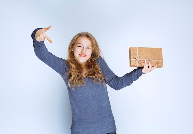 Белокурая девушка с картонной подарочной коробкой указывая ниже.