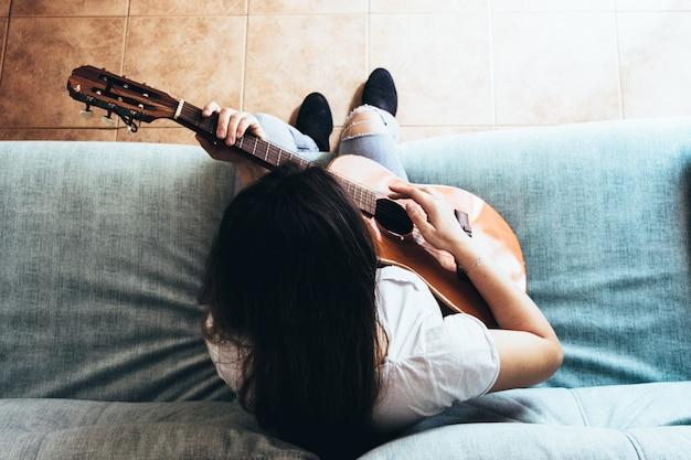 소파에 그녀의 스페인 기타를 연주하는 집에 갇힌 마스크를 가진 금발 소녀 바이러스 sars-cov-2에 대한 가정 격리 자동 검역. 유행성 코로나 바이러스.
