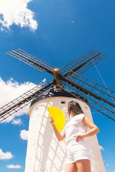 자신을 부채질하는 그녀의 손에 노란색 팬을 가진 금발 소녀. 전통적인 풍차 배경과 푸른 하늘