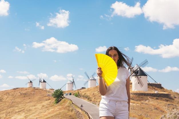 자신을 부채질하는 그녀의 손에 노란색 팬을 가진 금발 소녀. 백그라운드에서 전통적인 풍차입니다.