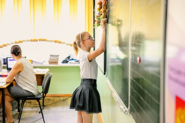 Blonde girl with big glasses sitting in classroom, studing, smiling. education on elementary school, first day at school