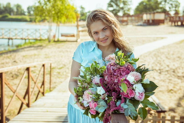 Blonde girl with bouquet in a blue dress