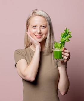 Blonde girl with celery juice on pink