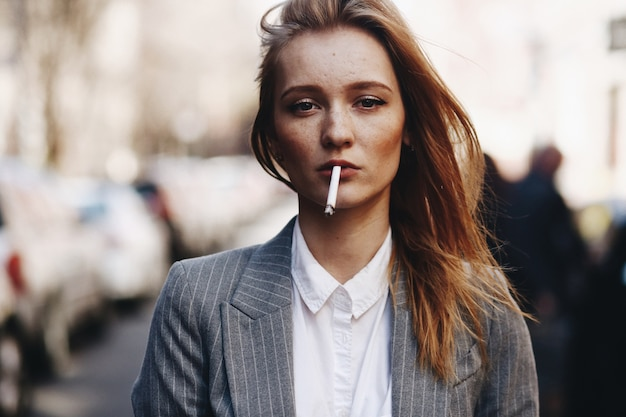 Blonde girl with cigar stands on the street
