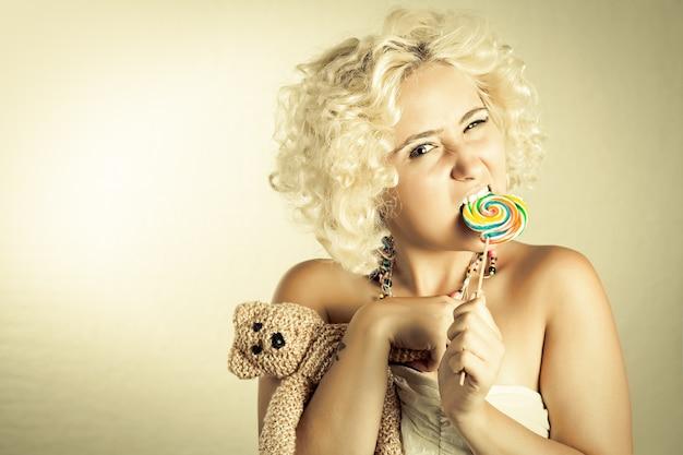 다채로운 롤리팝과 곰 장난감을 가진 금발 소녀 롤리팝을 물고 장난감을 들고 있는 여자