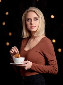 Blonde girl with cup of coffee and gingerbread cookie on wall with fairy lights
