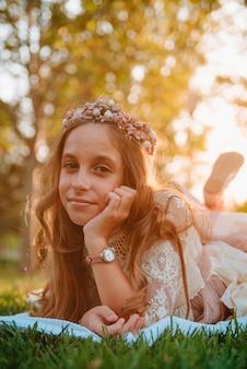 Блондинка с вьющимися волосами, одетая в платье для причастия, лежит на траве для фотографий