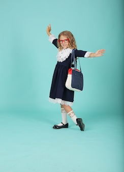 赤いフレームの眼鏡をかけている巻き毛のブロンドの女の子バッグと青い制服