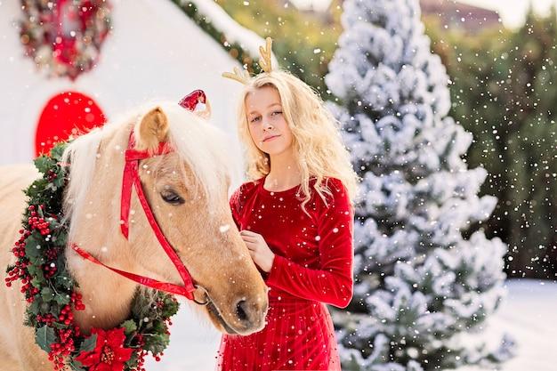 Блондинка с оленьими рогами в красном бархатном платье стоит с пони под снегом.