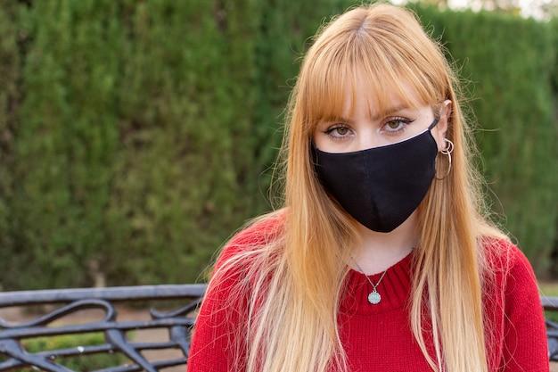 얼굴 마스크와 공원 벤치에 앉아 빨간 스웨터와 금발 소녀.