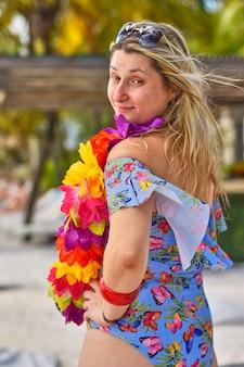 꽃 목걸이와 금발 소녀는 자연의 한가운데 포즈
