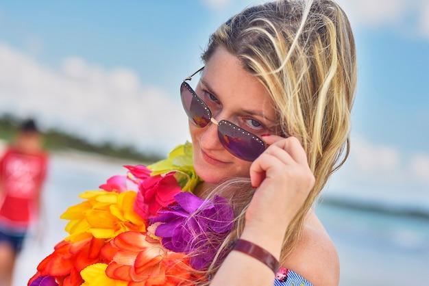 멕시코의 바다 근처에서 꽃 목걸이를 한 금발 소녀 포즈