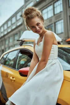 Blonde girl with flyaway hair in the background of new york city street with taxi cabs.