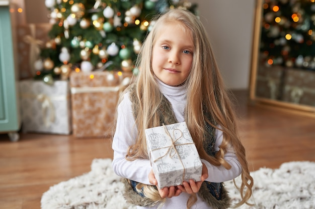 Blonde girl with gifts in the new year's interior
