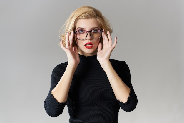 Blonde girl with glasses red lips black blouse cropped view glamor light background studio.
