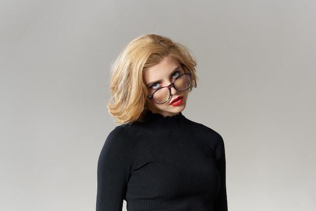 メガネの赤い唇とブロンドの女の子は黒いブラウストリミングビューグラマーライトスタジオです。高品質の写真